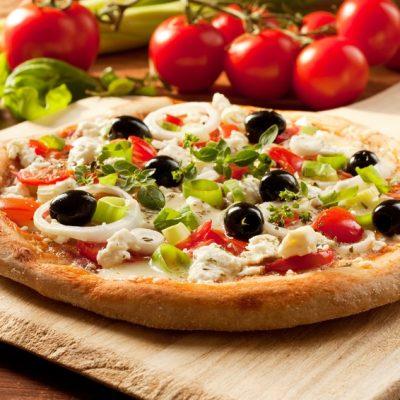 Griechische vegetarische Pizza mit Tomaten, Oliven, Poree und Zwiebeln
